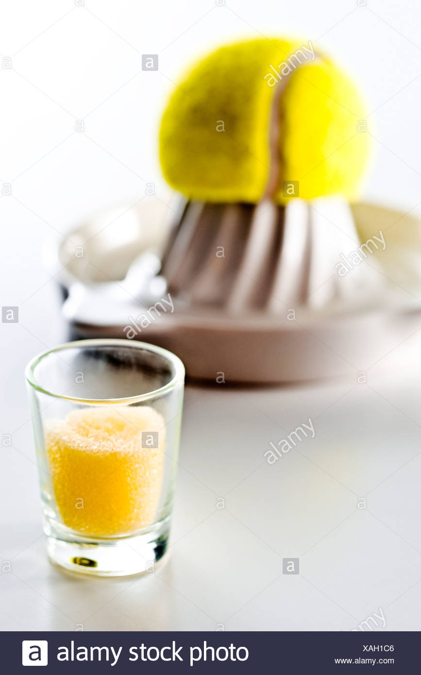 Food concept, fake glass of juice, tennis ball on juicer in background - Stock Image