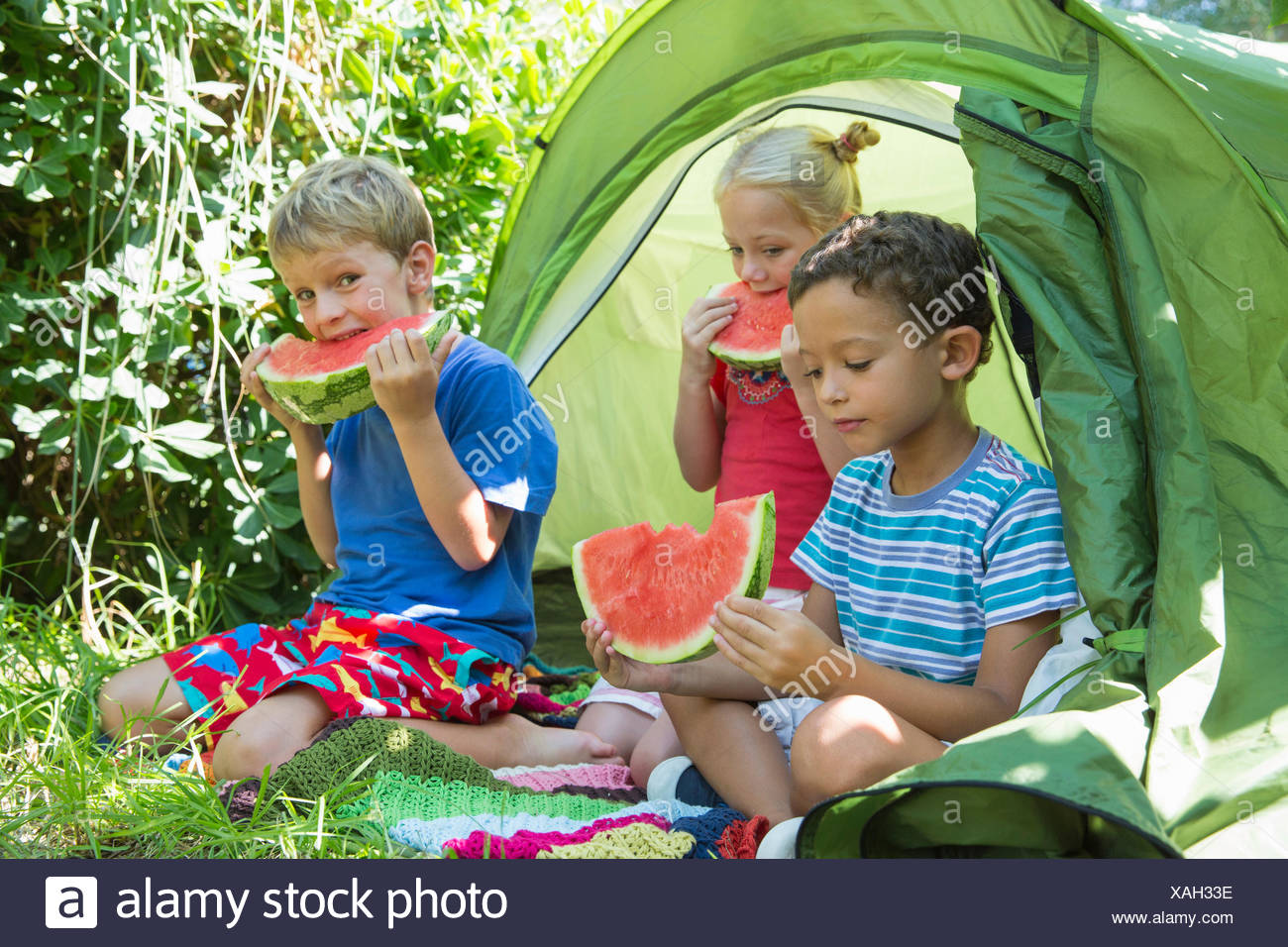 Three children eating watermelon slices in garden tent - Stock Image