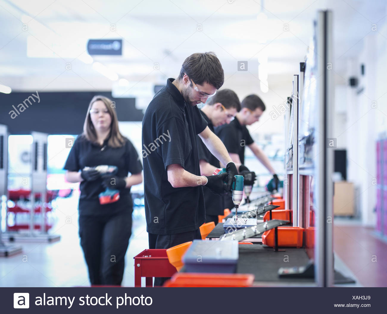 Apprentices working on training production line - Stock Image