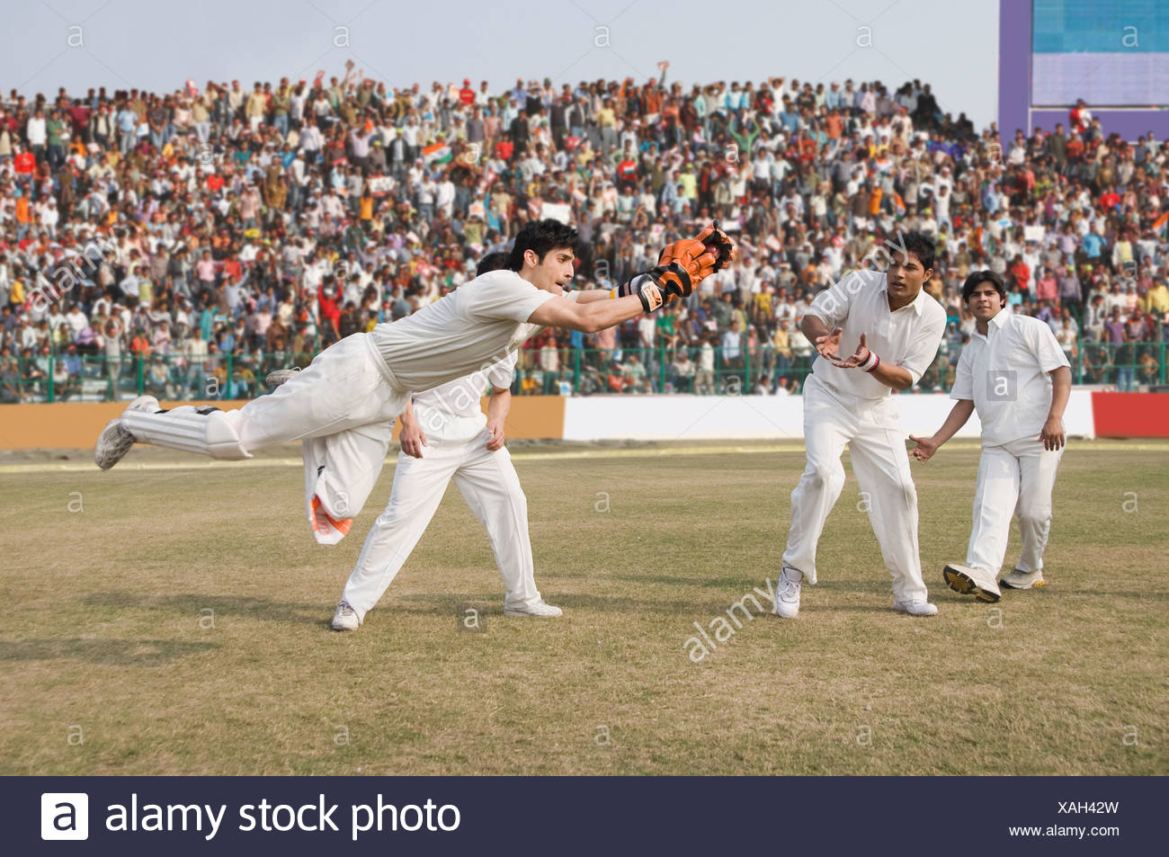 Cricket wicket keeper and fielders attempting for a catch - Stock Image