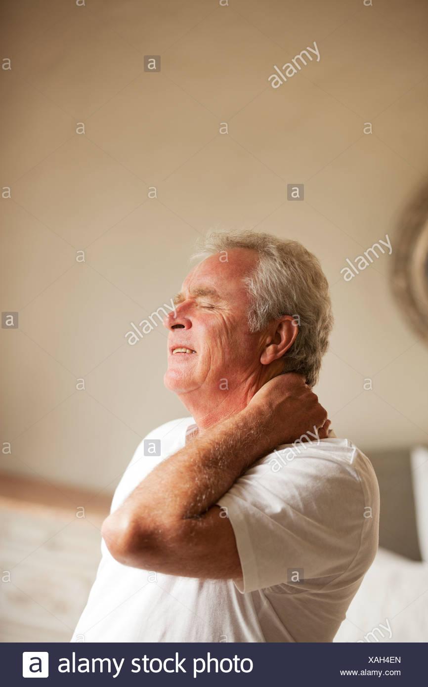 Senior man holding neck in pain - Stock Image