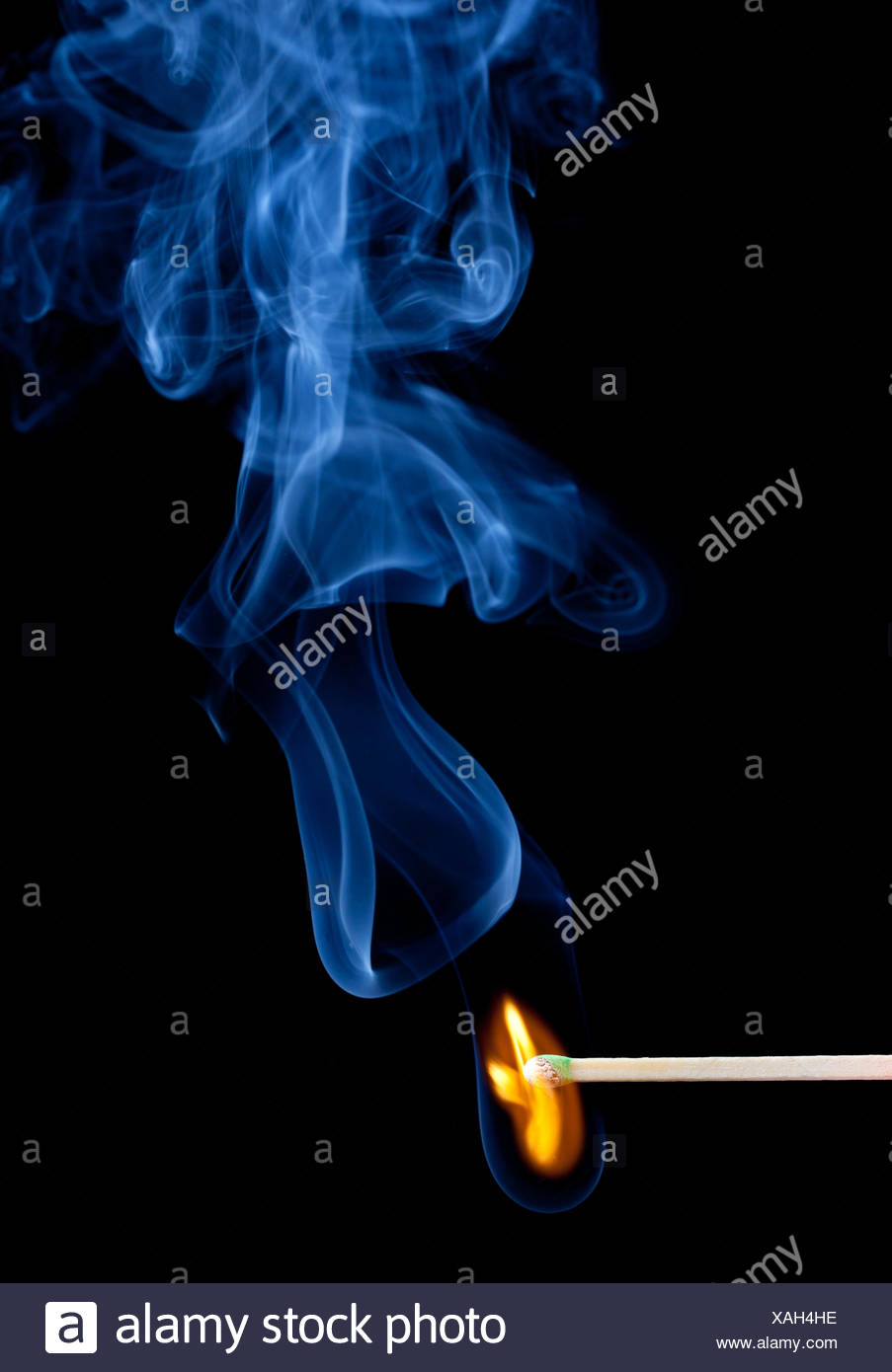 Green headed match starts to smoulder - Stock Image