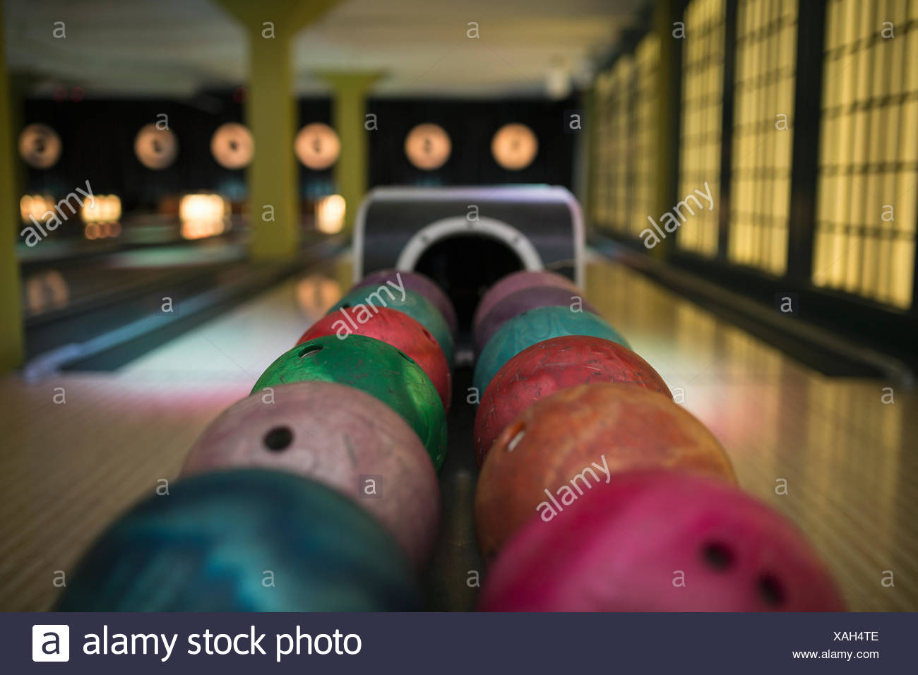 Multicolor bowling balls on rack at bowling alley - Stock Image