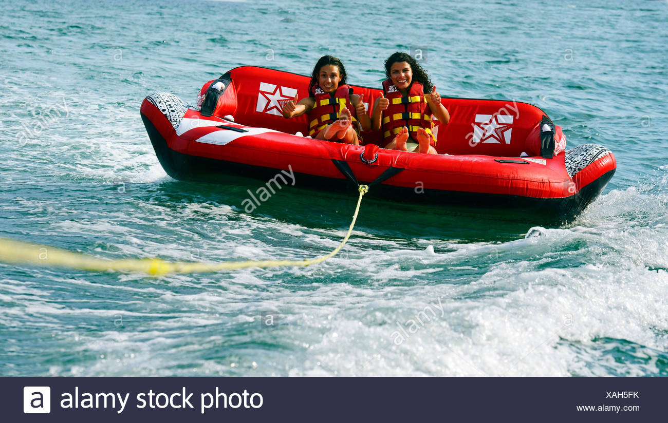 two girls are be pulled over the water with an air couch, France, Corsica Stock Photo
