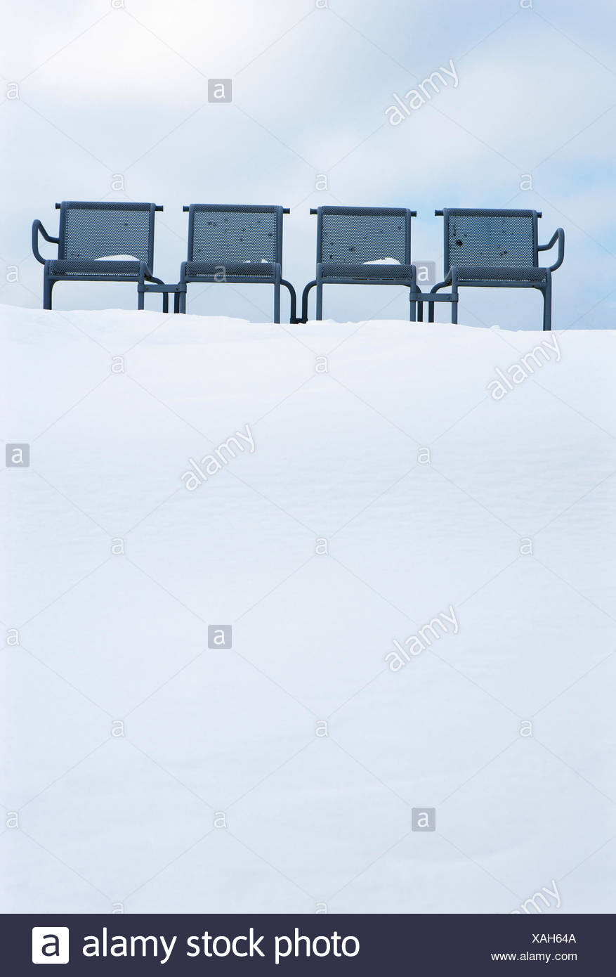 Empty row of seats in snow - Stock Image