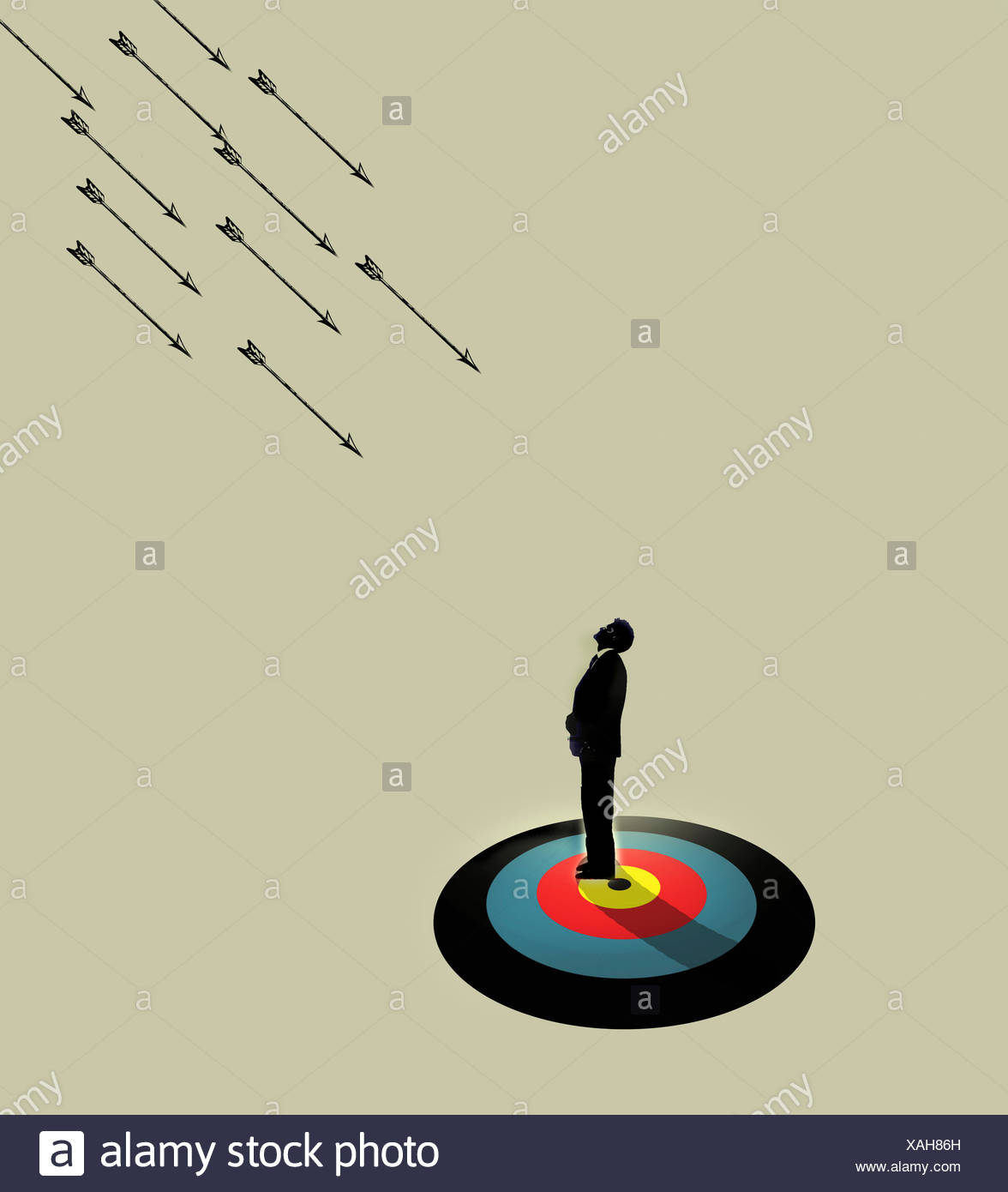 Businessman standing on target waiting for arrows to hit - Stock Image