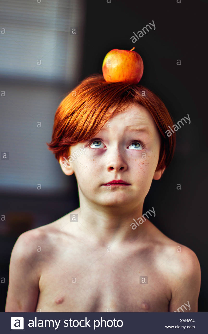 Boy balancing an apple on his head - Stock Image