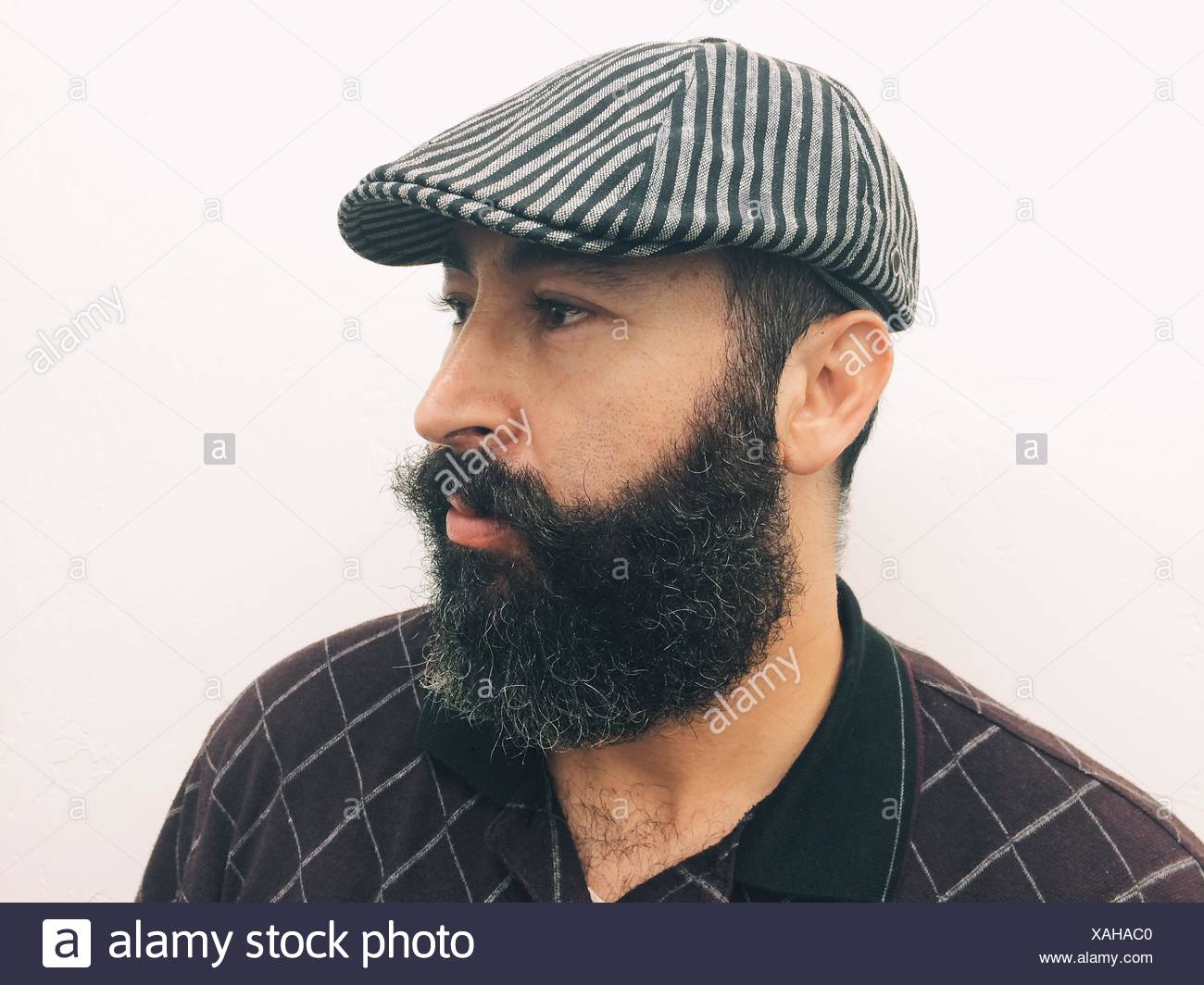 Side View Of Mature Man With Beard Wearing Hat Against White Background - Stock Image