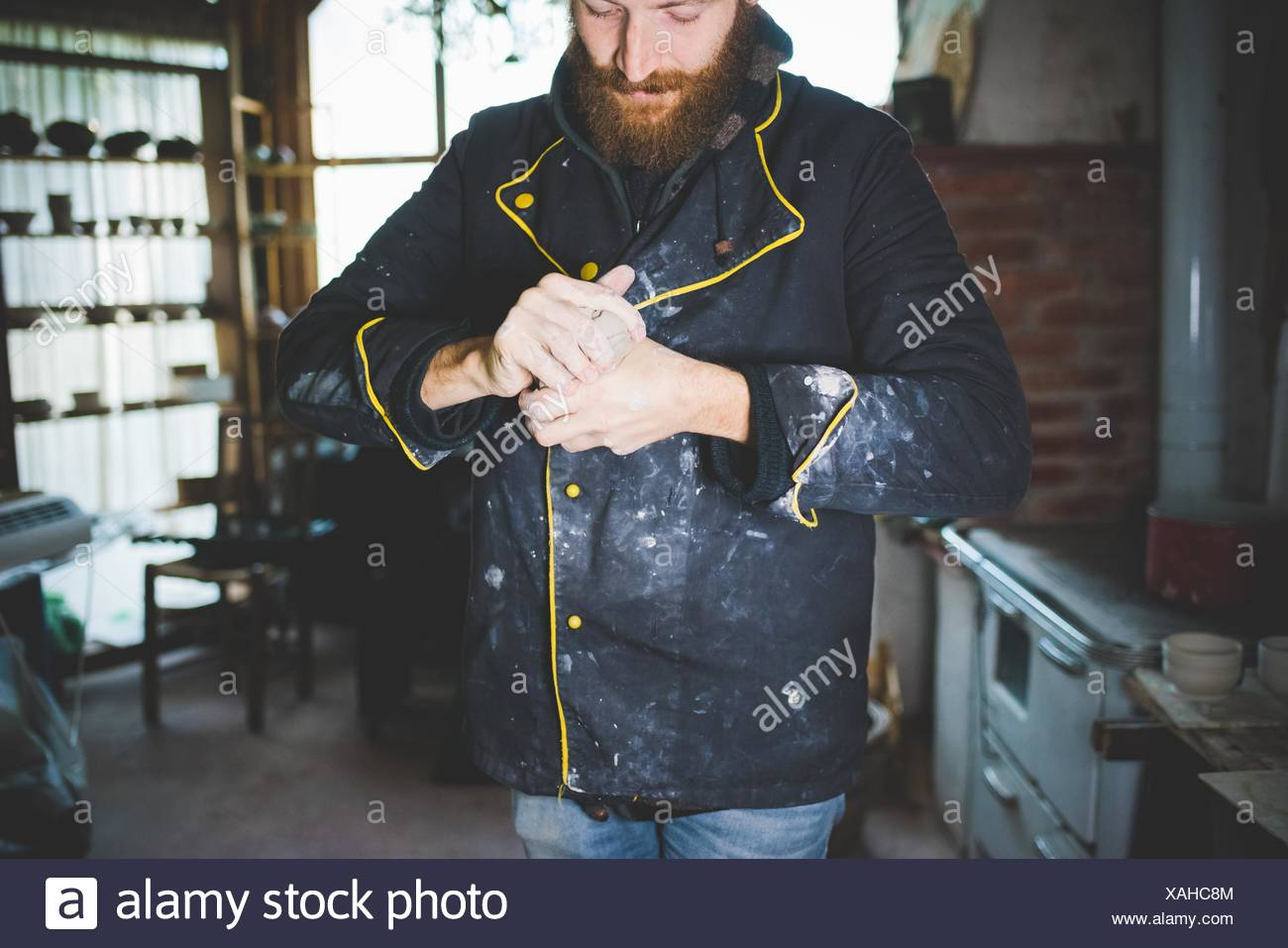 Bearded mid adult man squeezing clay in hands, looking down - Stock Image