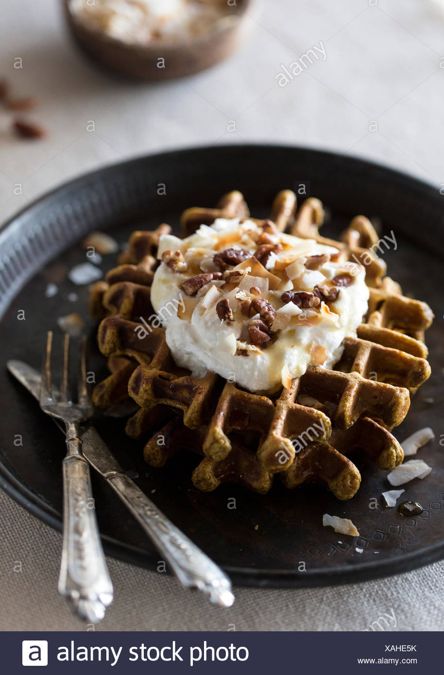 Spicy pumpkin waffles topped with coconut whipped cream, pecans, and maple syrup are photographed from the front. - Stock Image