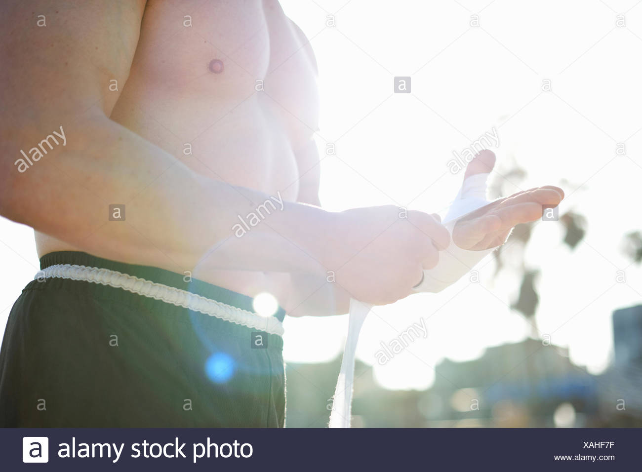 Low angle view of muscular mans mid section, applying tape grip to hand - Stock Image
