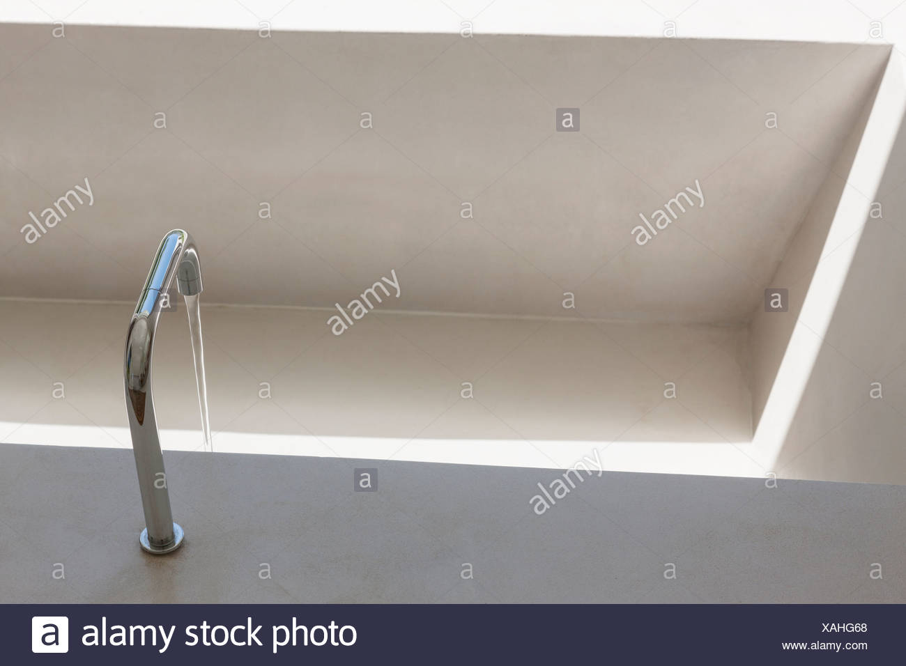 Water from faucet filling bathtub - Stock Image