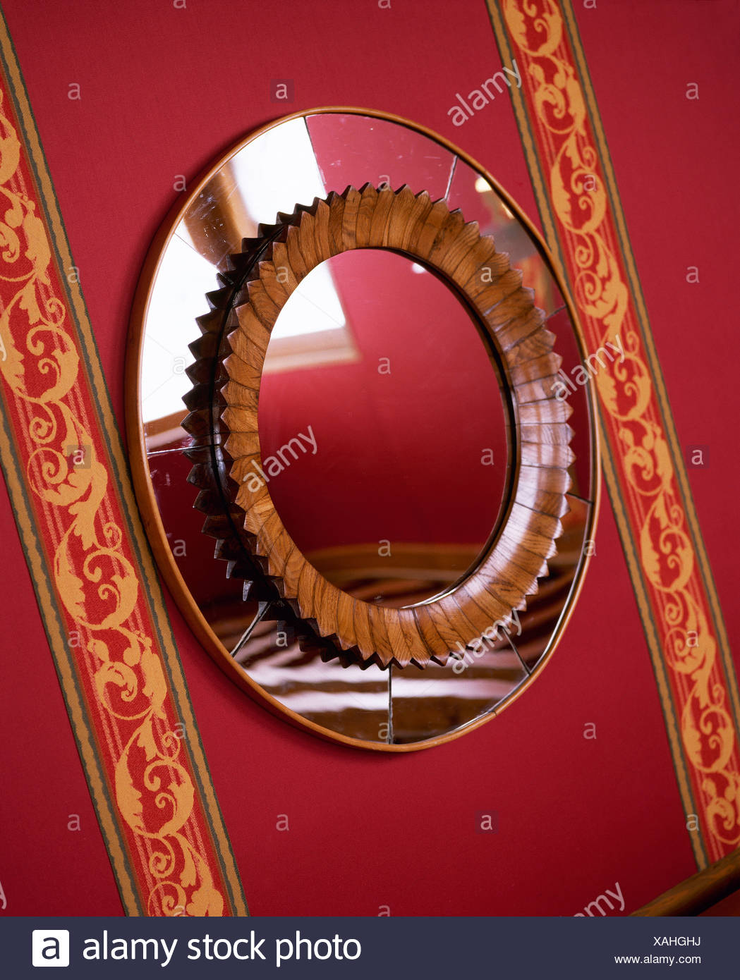 Close Up Of Decorative Circular Mirror On Red Wall With Patterned