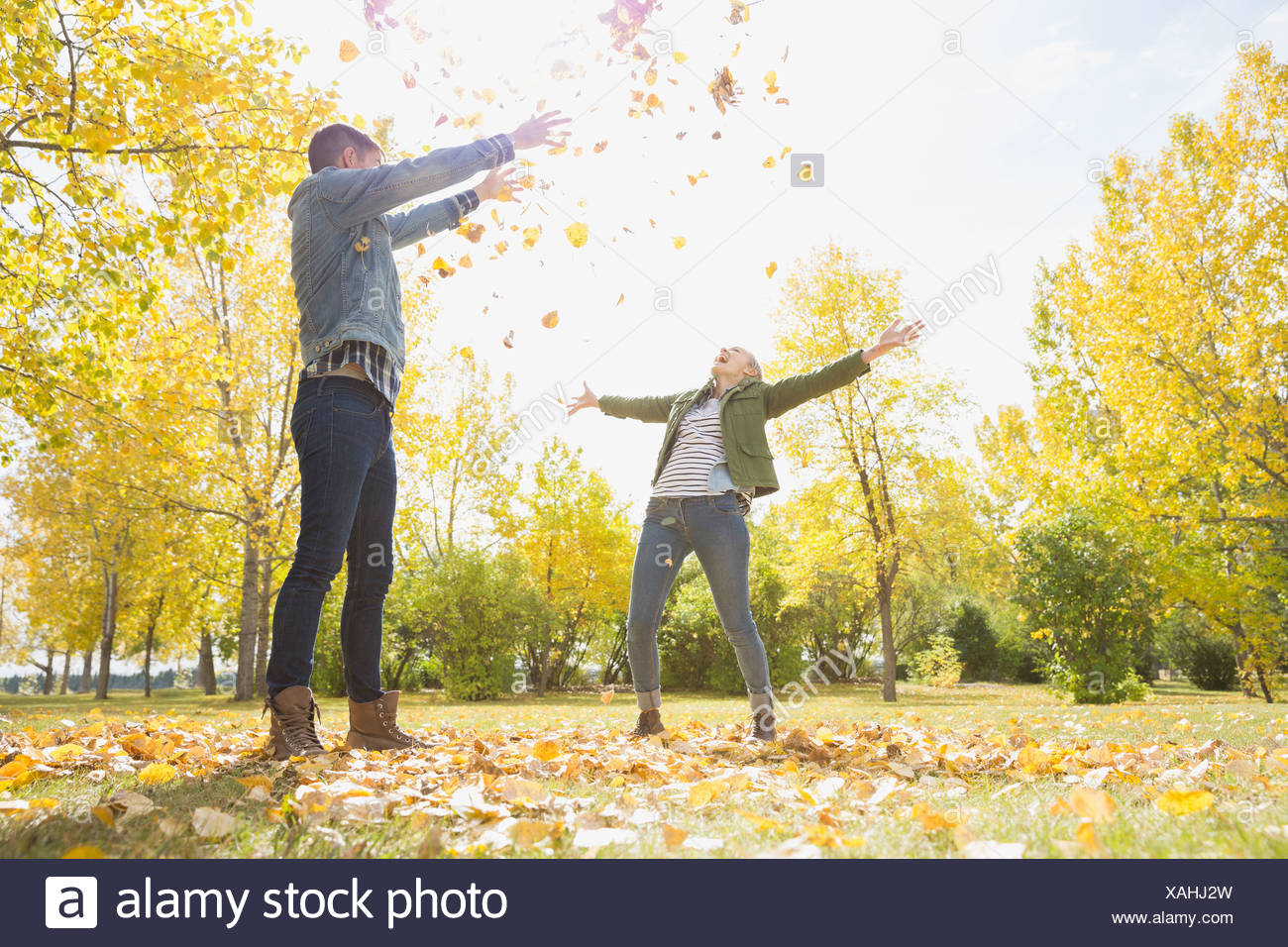Cheerful couple playing with autumn leaves - Stock Image
