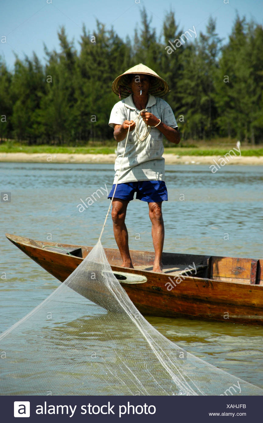 Fisherman with cone shaped hat fetching the net, smoking a cigarette, Hoi An, Vietnam, Southeast Asia - Stock Image