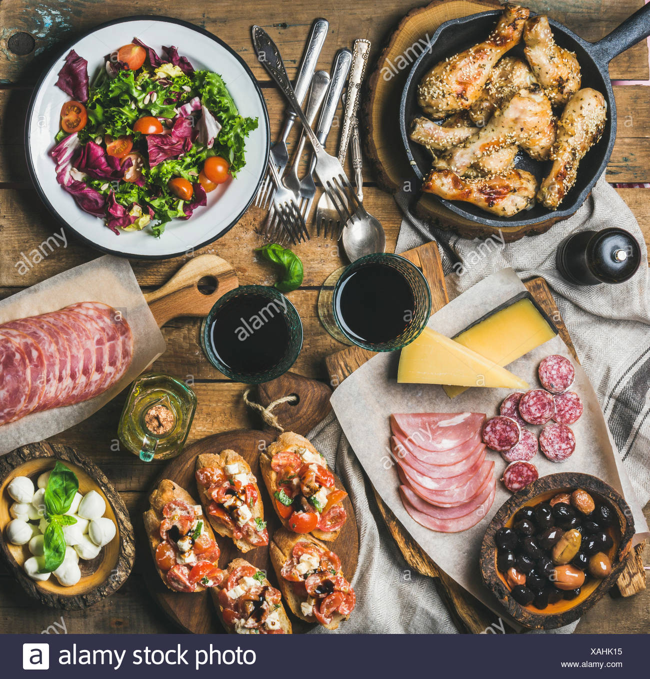 Home dinner, party table arrangement. Rustic table set with salad, olives, chicken, tomato, feta cheese brushettas, snacks and red wine, top view. Slo - Stock Image