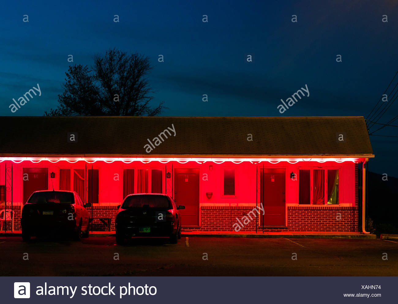 Budget motel exterior at dusk. - Stock Image
