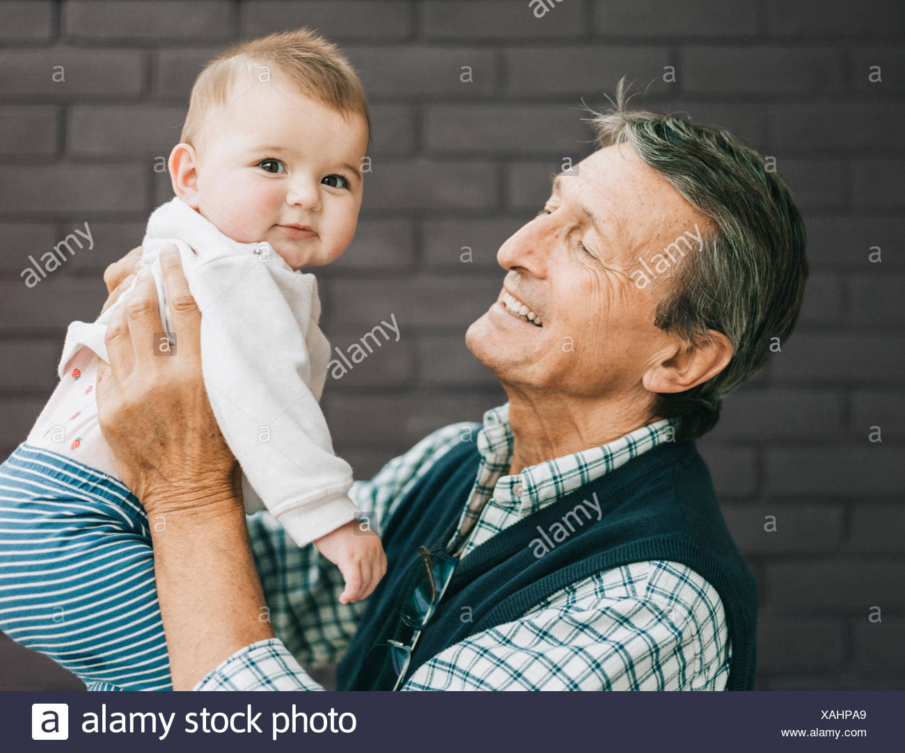 A grandfather and baby granddaughter. - Stock Image