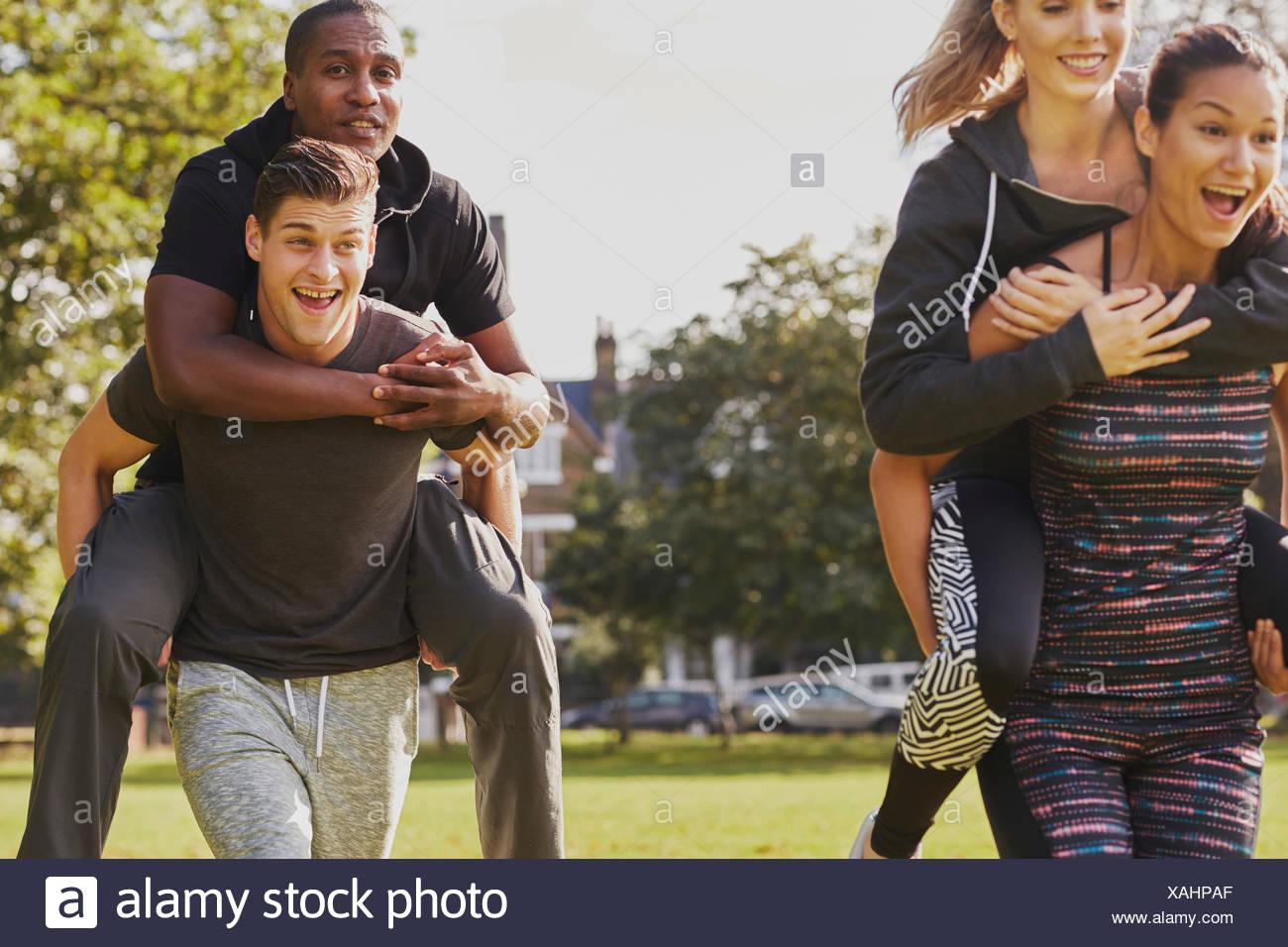 Men and women having fun training in park, having piggy back  race - Stock Image