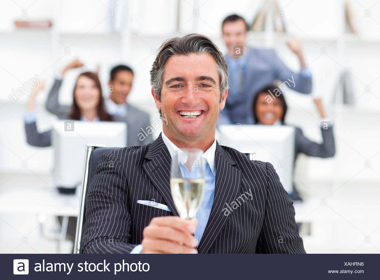 Prosperous manager and his team drinking champagne - Stock Image