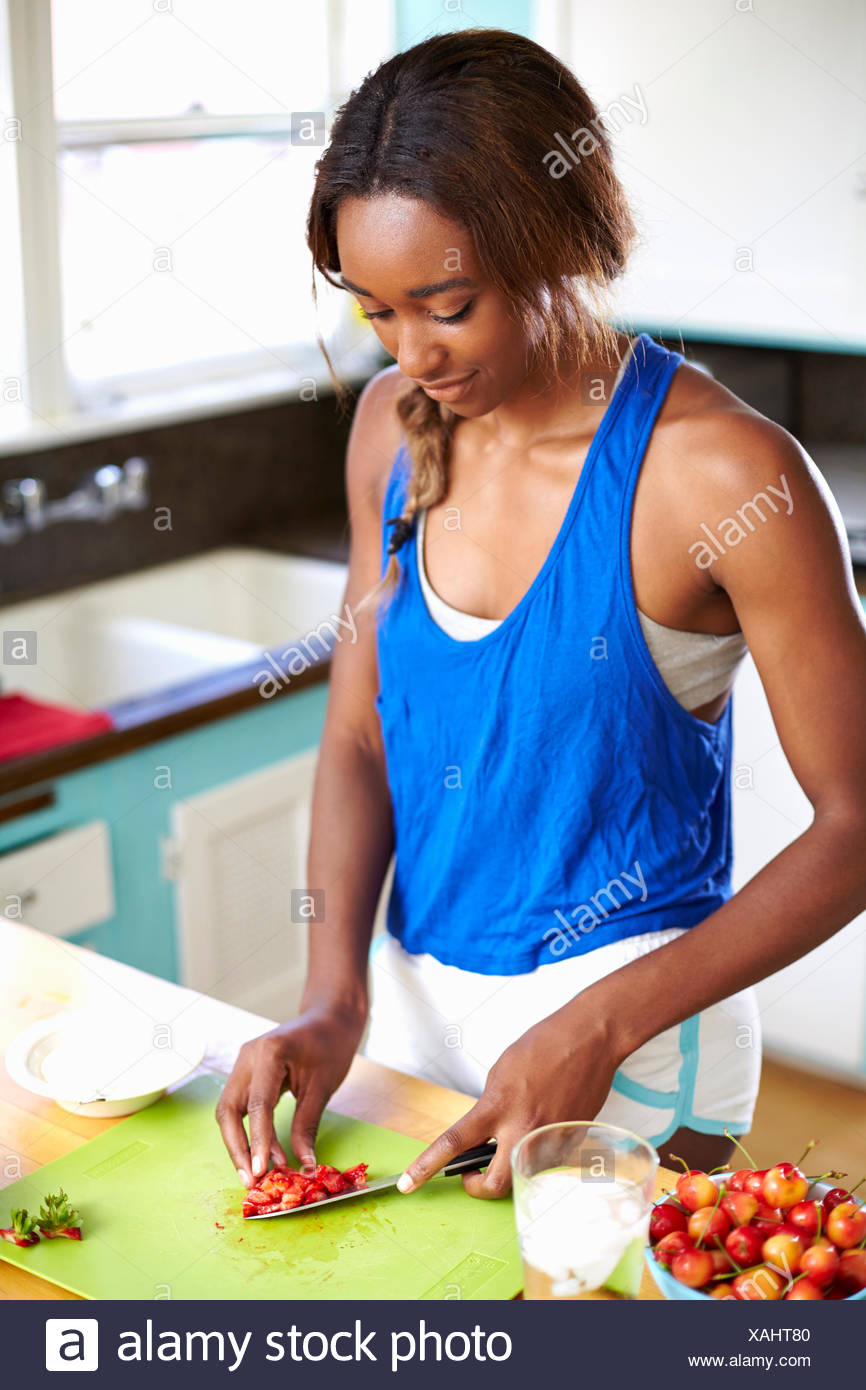 Young woman taking a training break, preparing fruit in kitchen - Stock Image