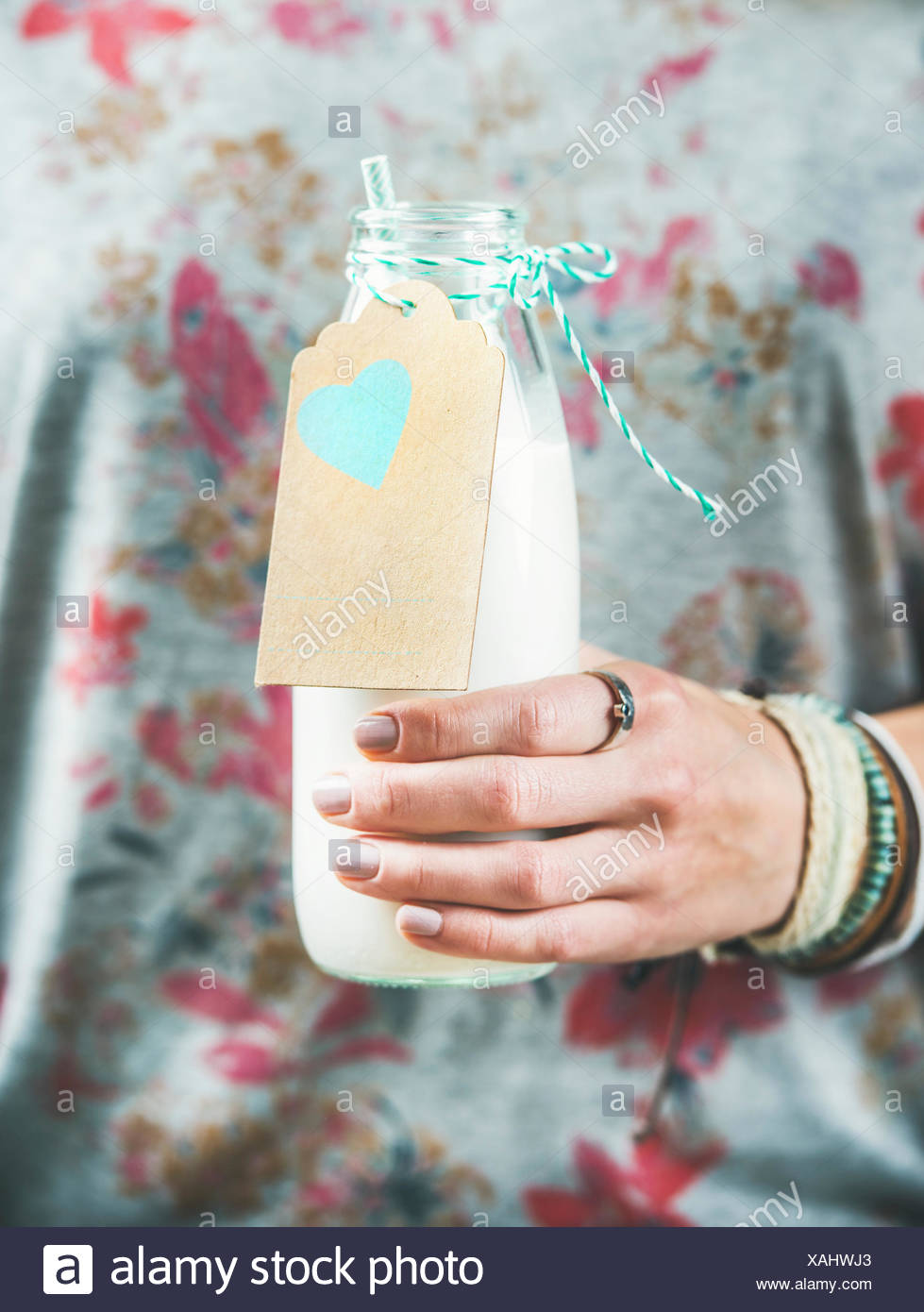 Young woman in grey t-shirt with floral pattern holding bottle of dairy-free almond milk in her hand. Clean eating, vegan, vegetarian, dieting, health - Stock Image