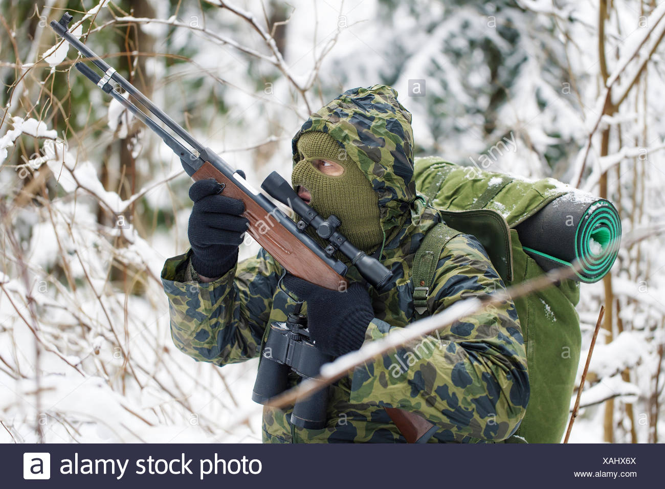 Hunter with optical rifle hidden in the backwoods - Stock Image