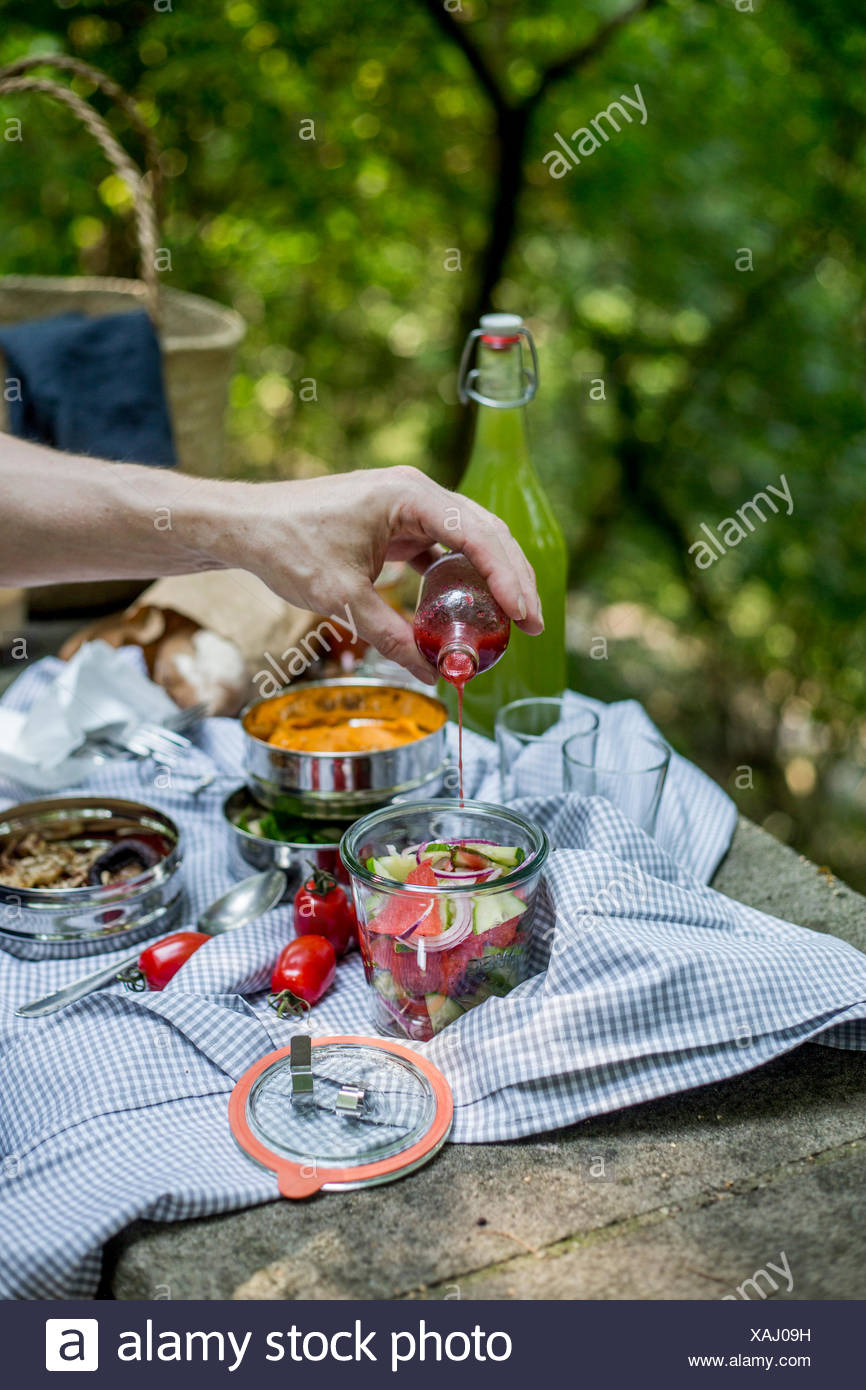 Hand pouring dressing on a salad at a picnic in the park - Stock Image
