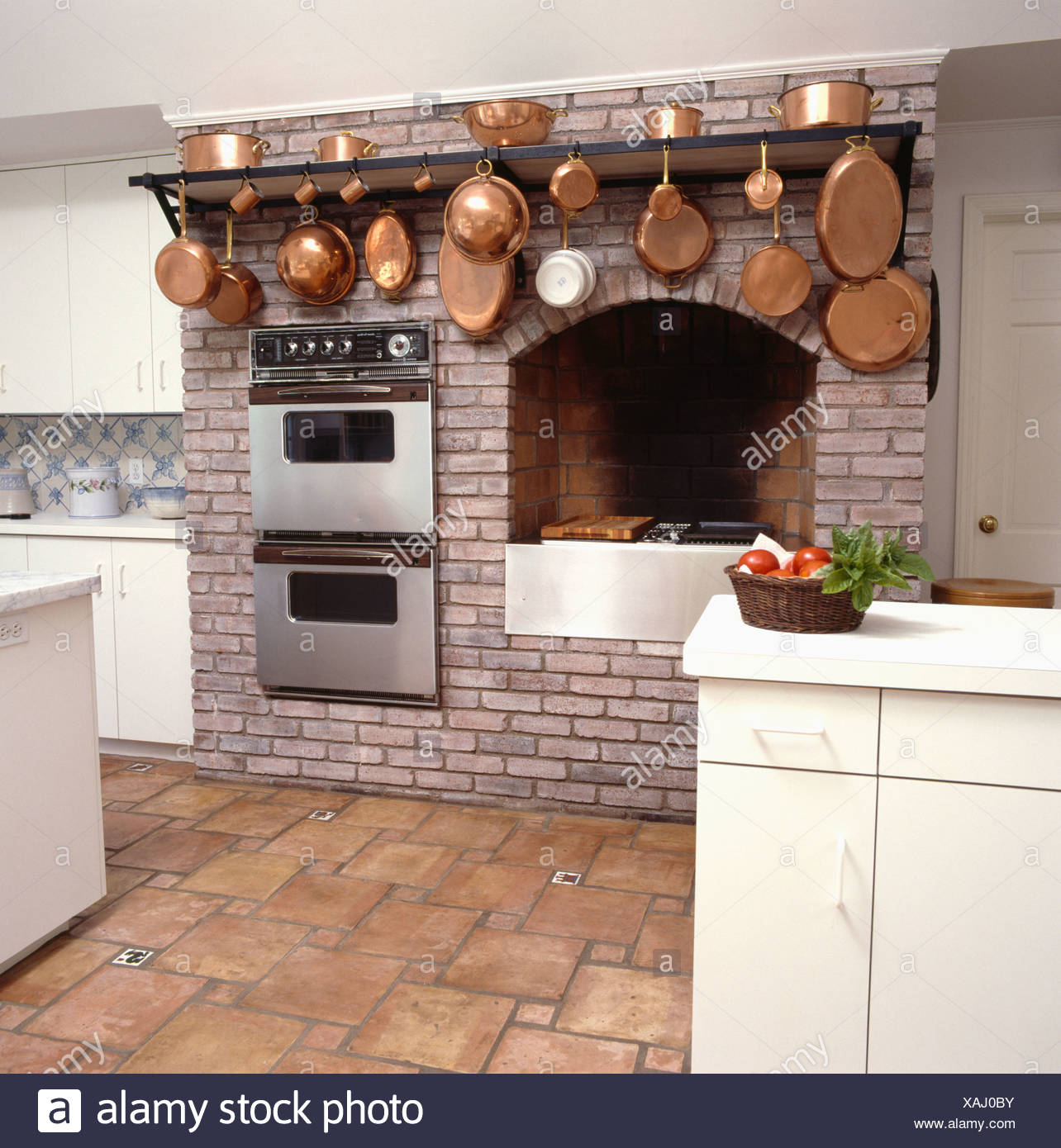 Copper Pans On Rack Above Double Ovens And Hob Fitted Into