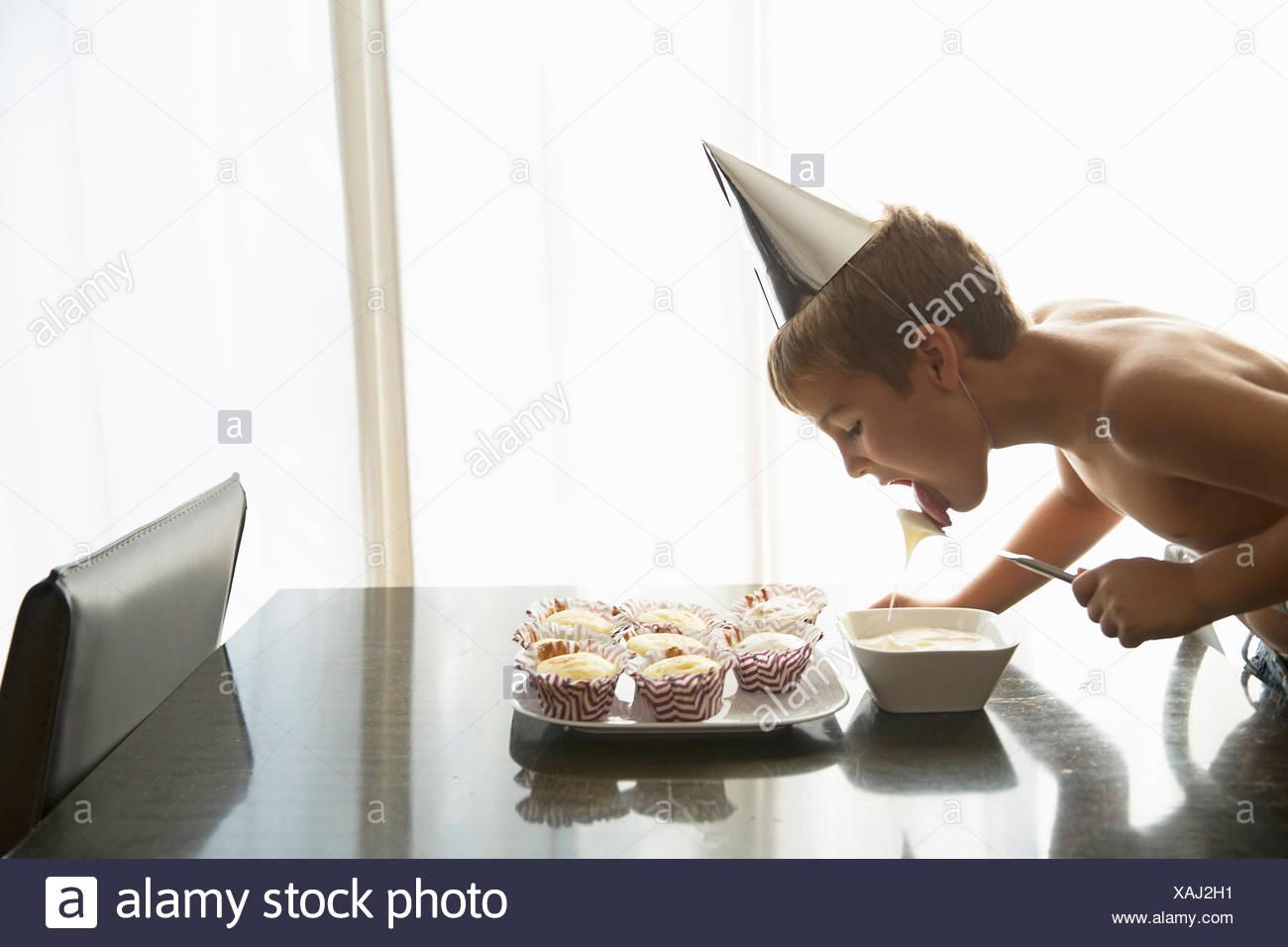 Boy licking cupcake topping at home - Stock Image