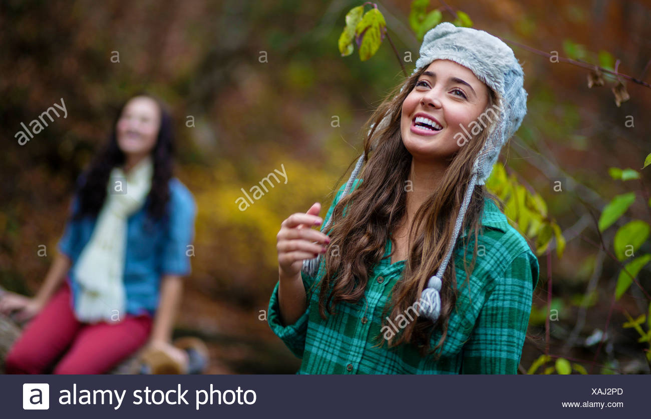 A young woman smiles while looking off camera in a riverbed near Lake Chinnabee, Alabama. - Stock Image