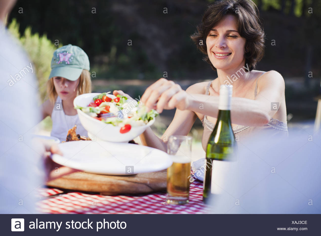Mother serving salad at picnic - Stock Image