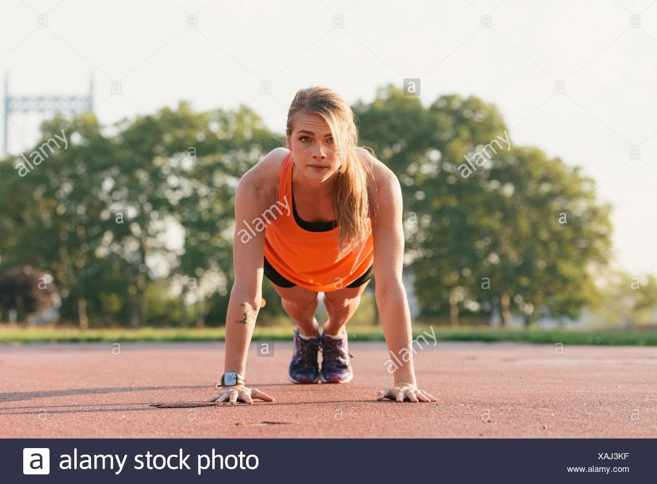 Young woman working out, doing press-ups, outdoors - Stock Image