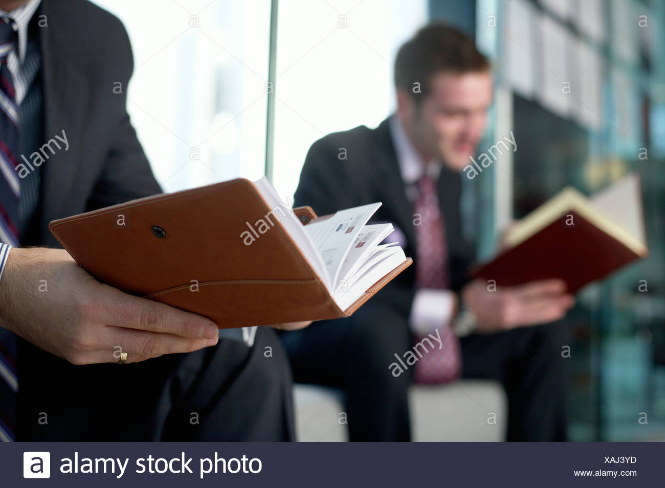 Two Businessmen looking in their diaries - Stock Image