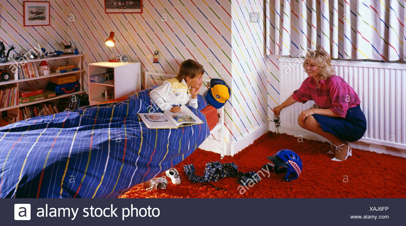 Mother and son in the child's bedroom, Mother turning down the radiatwhile the son is reading in bed - Stock Image