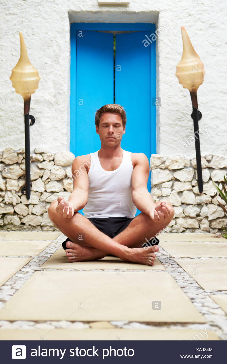 Man Meditating Outdoors At Health Spa Stock Photo