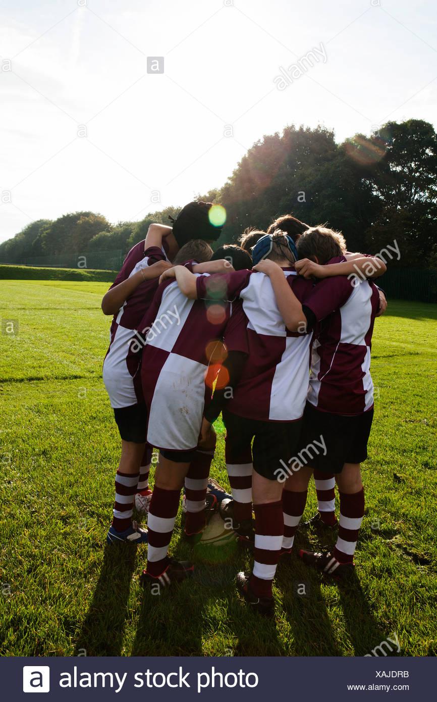 Teenage schoolboy rugby team in huddle - Stock Image