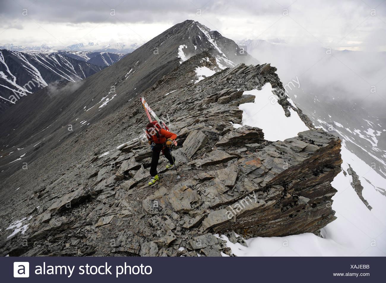 Backpacker climbs the West Ridge of Mt. Chamberlin in the Brooks Range, ANWR, Arctic Alaska, Summer - Stock Image