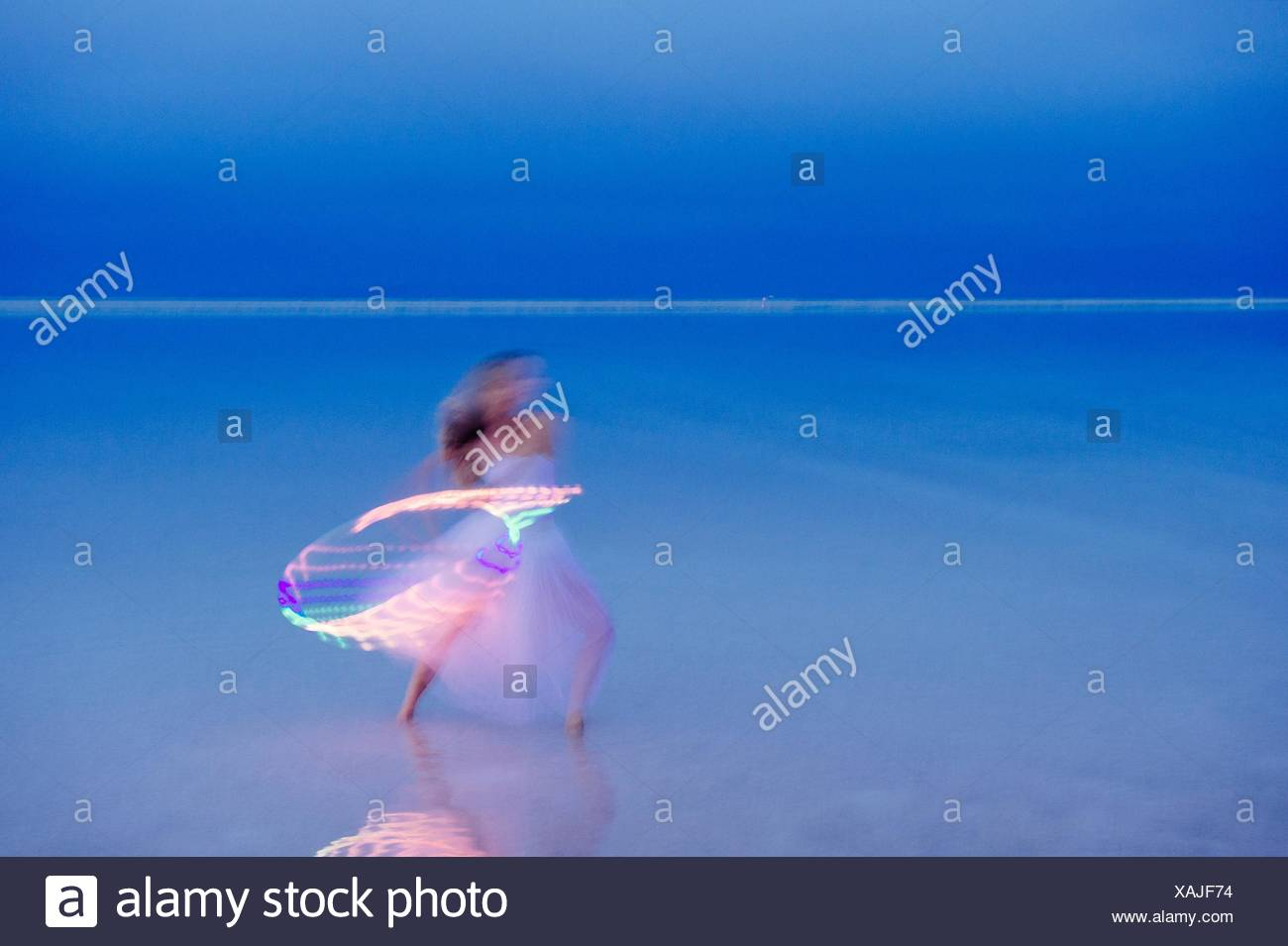 Woman wearing party dress poised with illuminated hoop at dusk - Stock Image