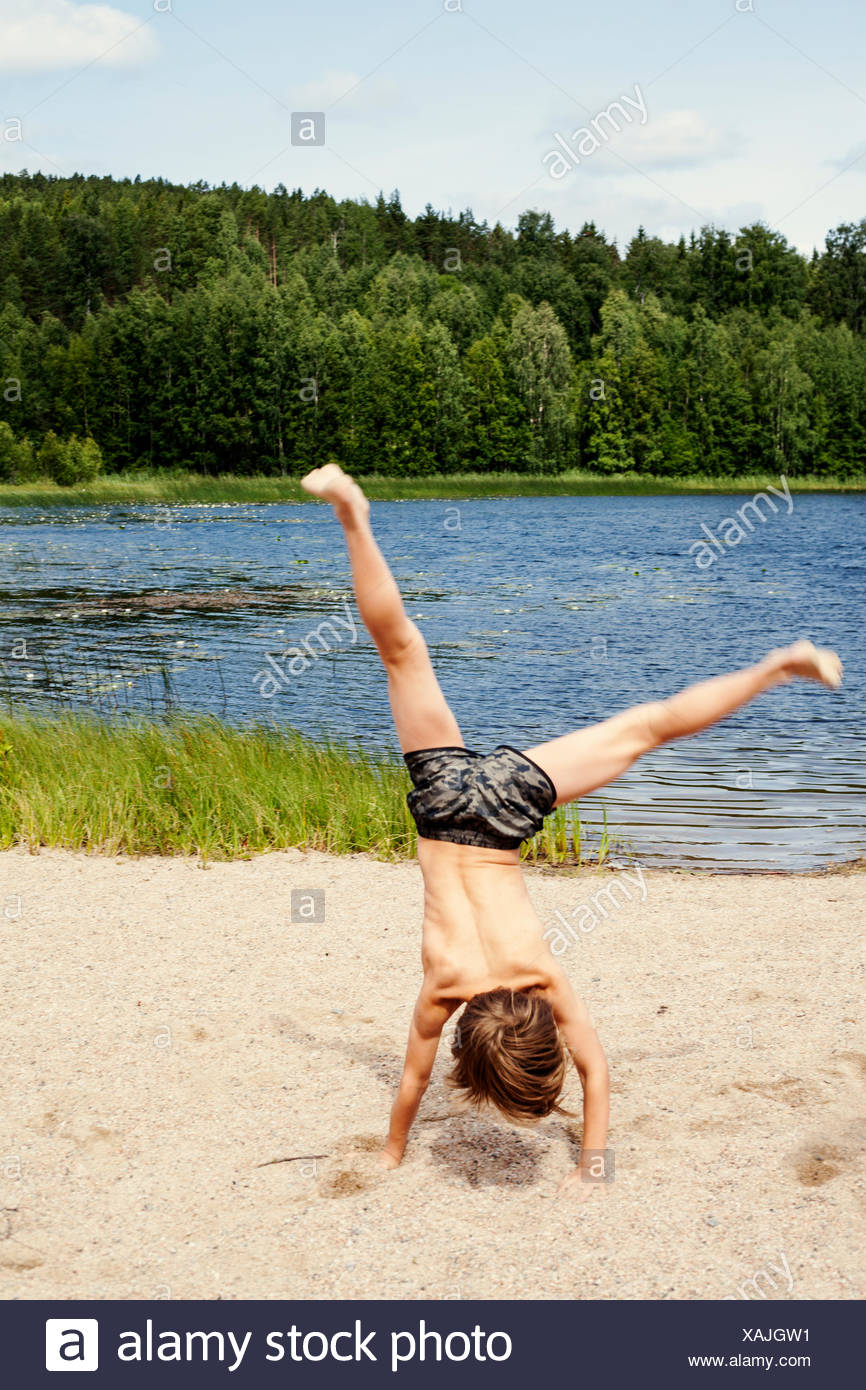 Sweden, Uppland, Runmaro, Barrskar, Boy (6-7) doing cartwheel on beach - Stock Image