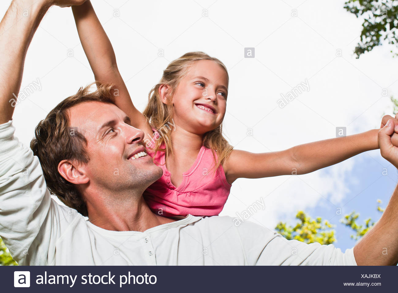 Father carrying daughter in park - Stock Image
