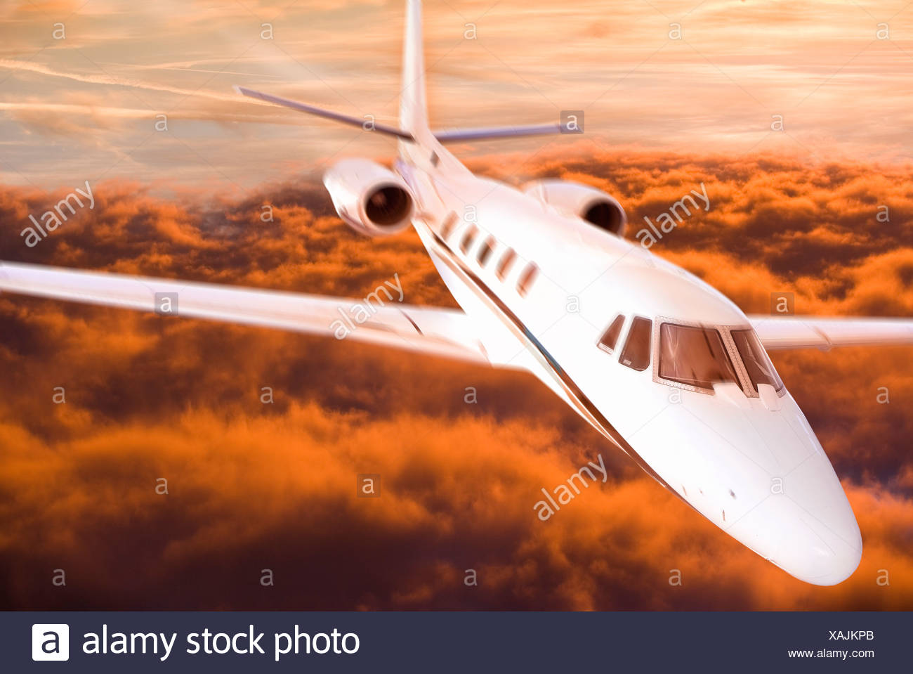 Airplane flying over orange clouds - Stock Image