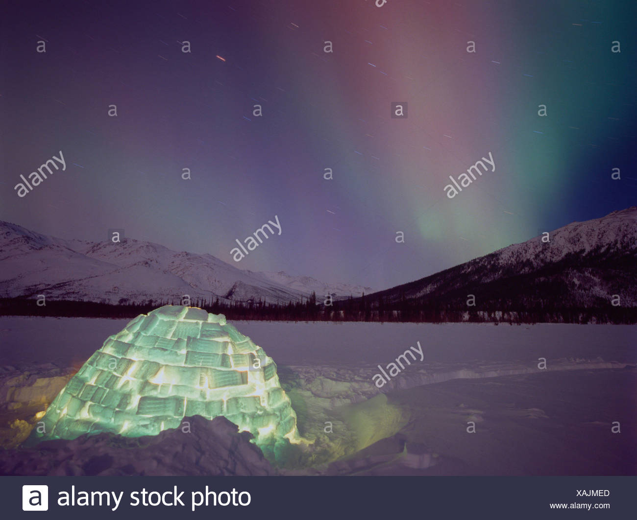 Celestial lights over an igloo in Alaska - Stock Image