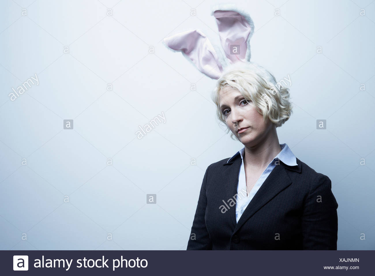 Studio portrait of blond businesswoman wearing bunny ears - Stock Image