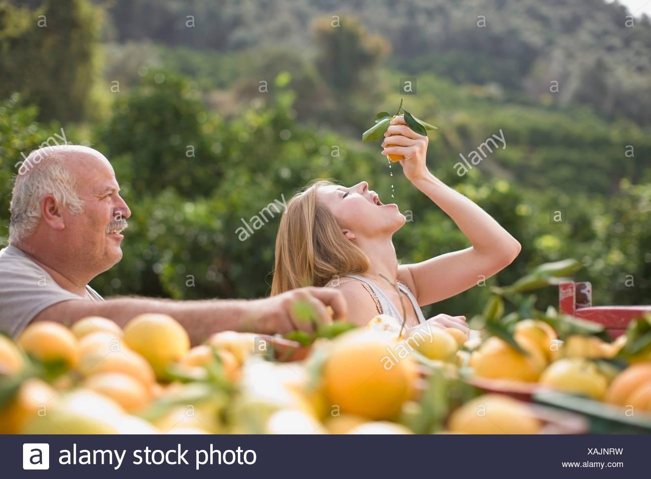 Girl squashing an orange - Stock Image