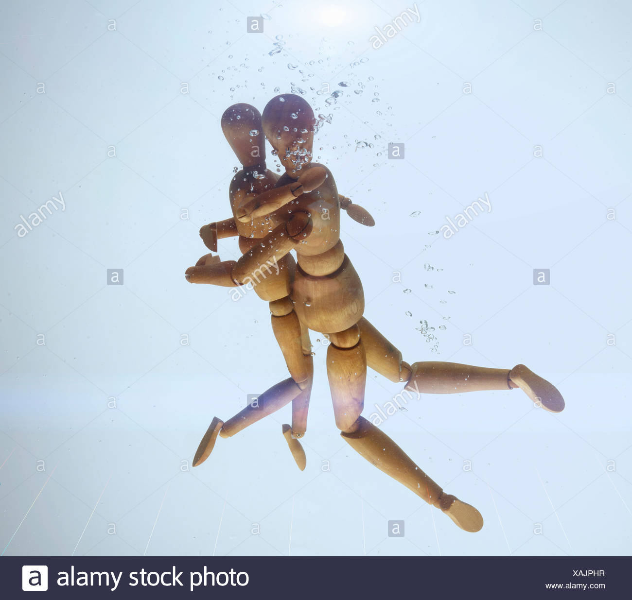 Wooden figurines hugging in water - Stock Image