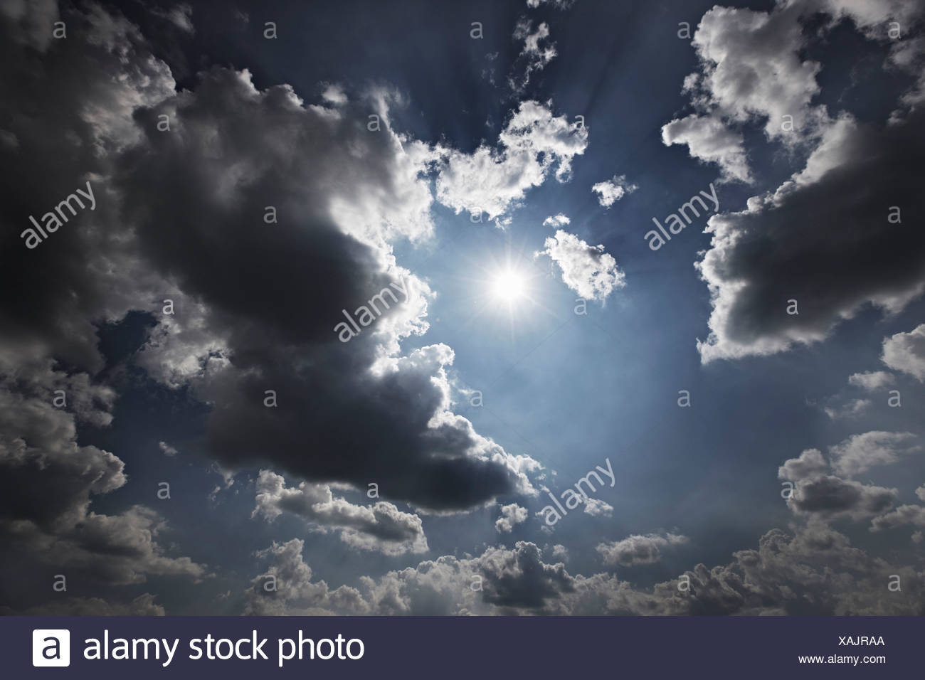 Sun and clouds in blue sky - Stock Image