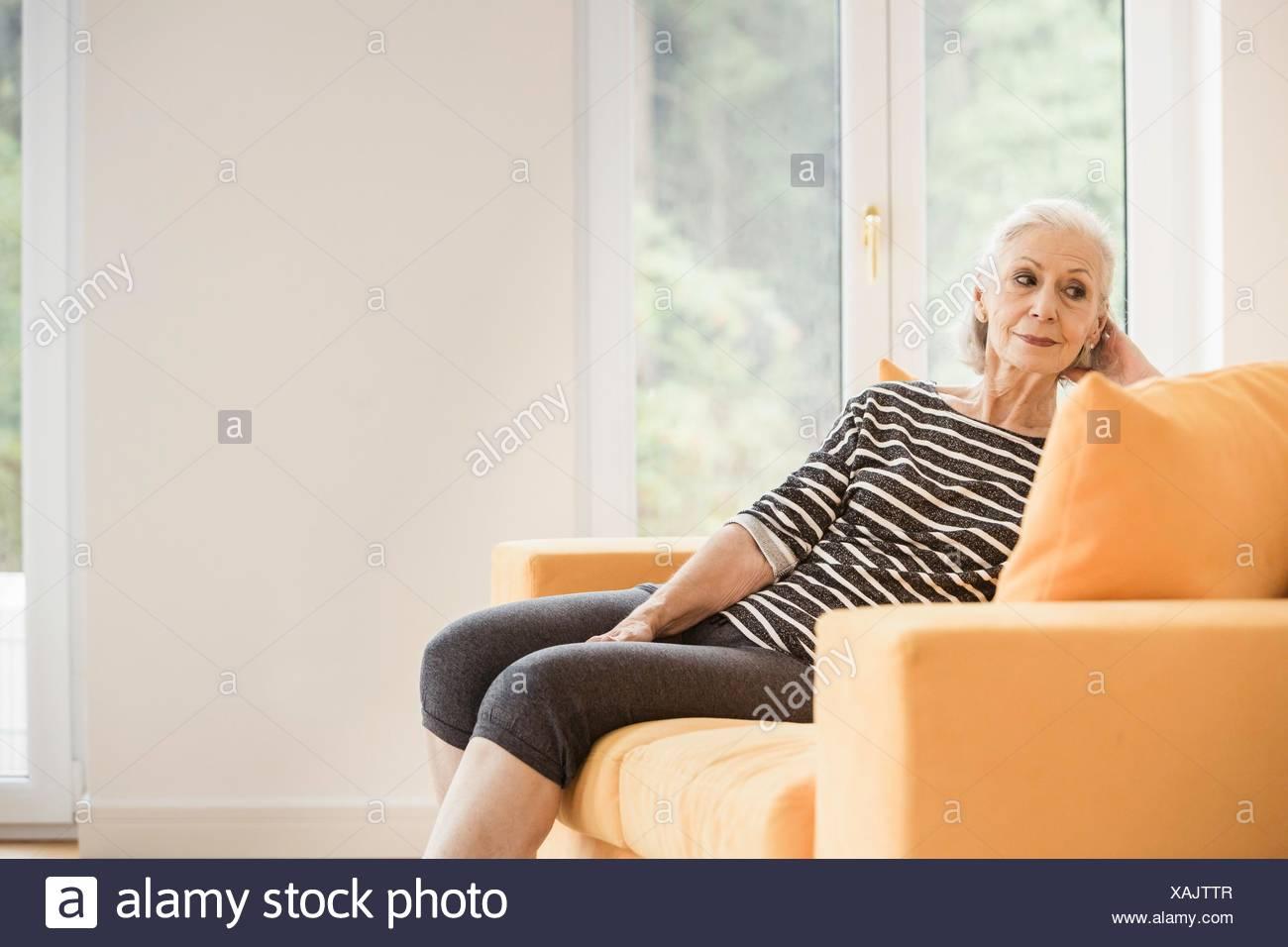Senior woman taking a break from exercising on living room sofa - Stock Image