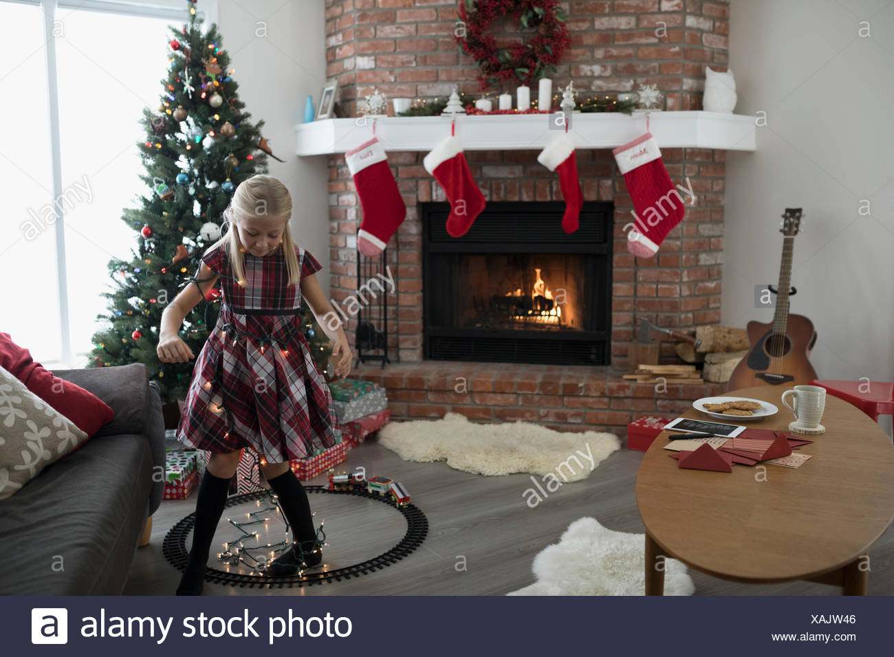 buy popular b2d22 d5afe Girl wrapped in Christmas tree string lights near fireplace ...