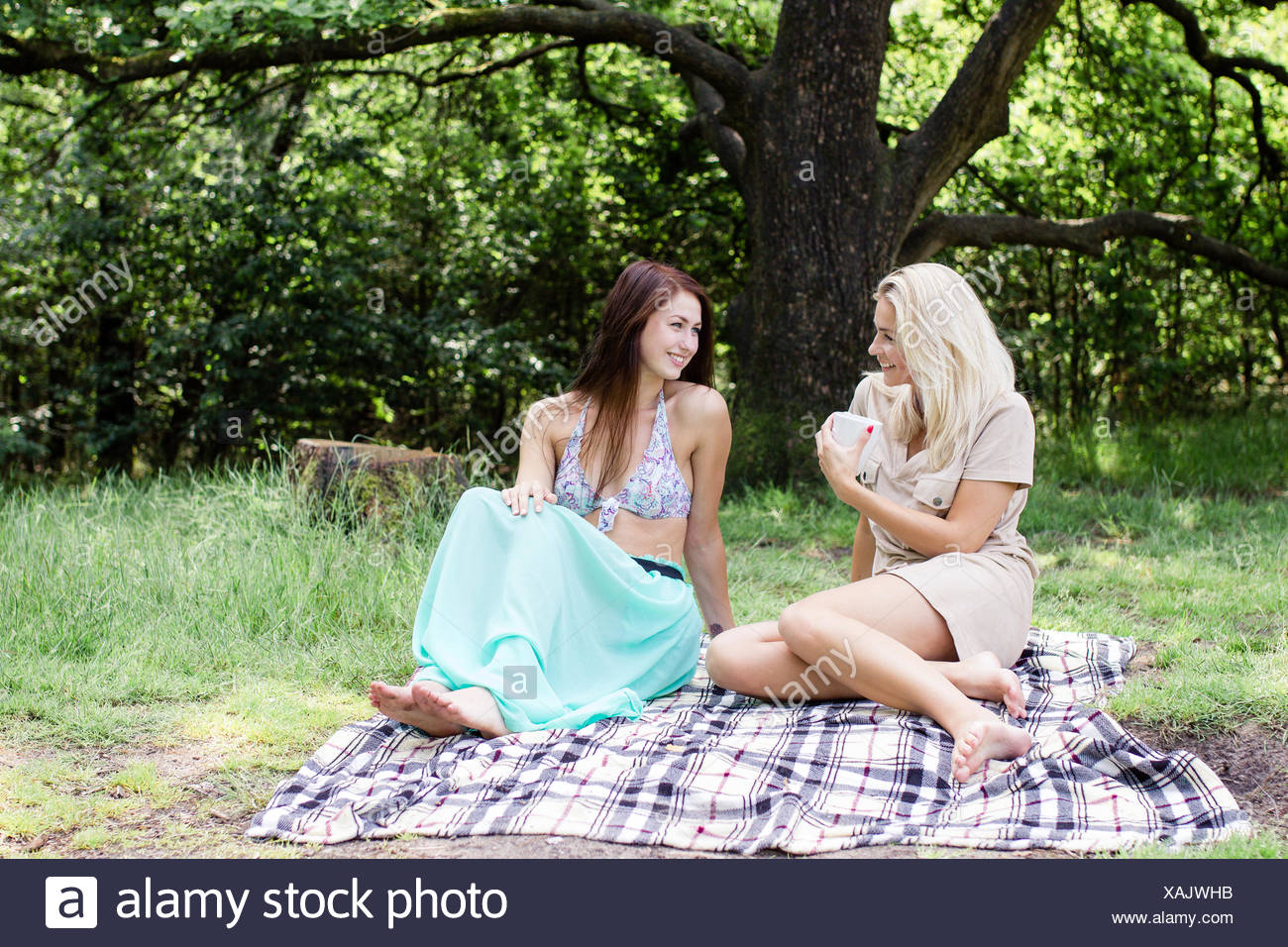 Two woman sitting on a picnic blanket talking - Stock Image